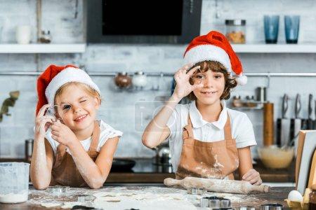 adorable kids in santa hats preparing christmas cookies and smiling at camera