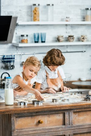 Photo for Adorable little children in aprons preparing cookies together - Royalty Free Image