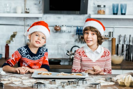 Photo for Cute happy kids in santa hats preparing ginger cookies and smiling at camera - Royalty Free Image