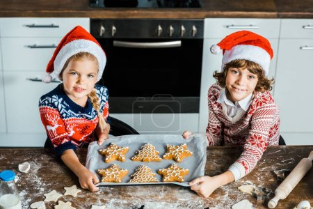 Photo for High angle view of cute happy kids in santa hats holding baking tray with ginger cookies and smiling at camera - Royalty Free Image