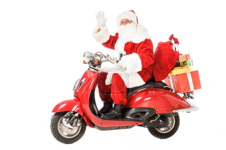 santa claus riding vintage red scooter and waving at camera isolated on white