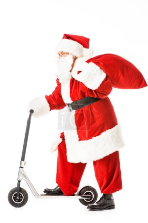 side view of santa claus with sack riding scooter isolated on white