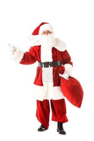 Photo for Santa claus holding sack and pointing away while looking at camera isolated on white - Royalty Free Image