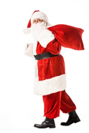 side view of santa claus walking with sack and looking at camera isolated on white