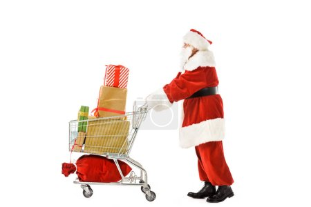 Photo for Side view of santa claus walking with shopping cart full of christmas gift boxes isolated on white - Royalty Free Image