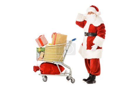 Photo for Side view of bewildered santa claus with shopping cart looking at camera isolated on white - Royalty Free Image