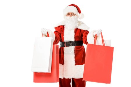 Photo for Santa claus standing with paper bags in hands and looking at camera isolated on white - Royalty Free Image