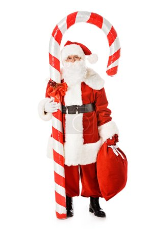 santa claus with giant candy cane and sack looking at camera isolated on white
