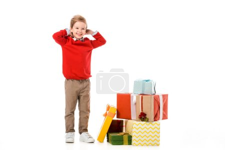 smiling little kid with pile of christmas gifts isolated on white