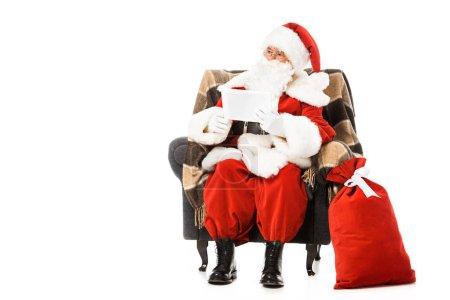 Foto de Santa claus sentado en sillón con tableta y mirando lejos, aislado en blanco - Imagen libre de derechos