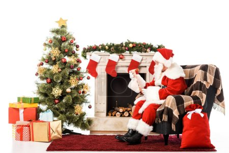 santa claus with letter sitting in armchair near fireplace and christmas tree isolated on white