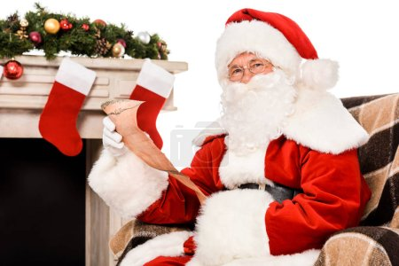 santa claus with letter sitting in armchair near fireplace and looking at camera isolated on white