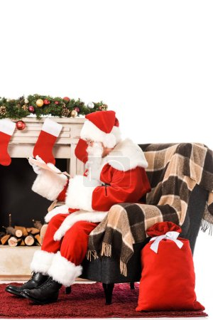 santa claus reading letter while sitting in armchair near fireplace isolated on white