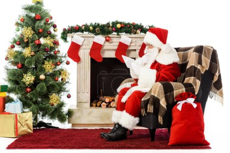 Photo for Santa using tablet while sitting in armchair near fireplace isolated on white - Royalty Free Image