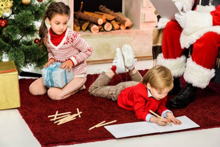 cropped shot of kids unpacking gifts and drawing on floor in front of santa
