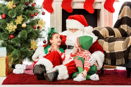 Photo for Santa embracing happy kids while they sitting on floor near fireplace together - Royalty Free Image
