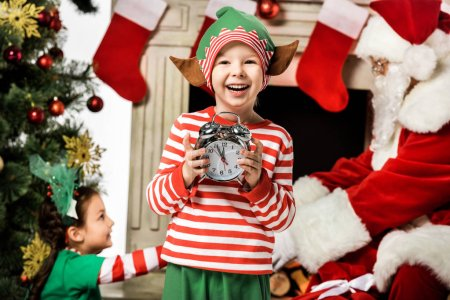 adorable little kid holding alarm clock with his sister and santa passing gift box on background