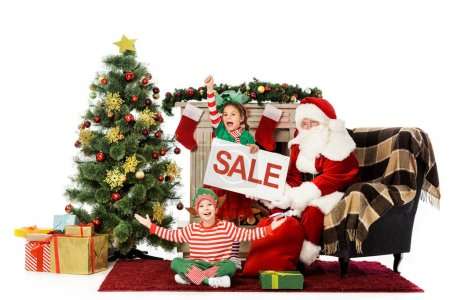 happy kids in elf costumes and santa holding sale banner, christmas shopping