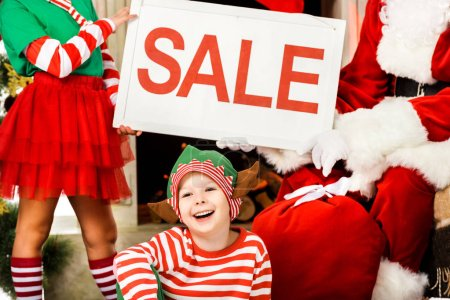 copped shot fo kids in elf costumes and santa holding sale banner, christmas shopping