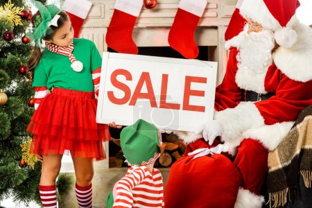 kids in elf costumes and santa holding sale banner, christmas shopping