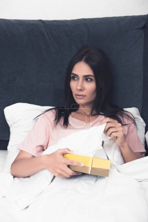 sick young woman taking paper napkin out of box while sitting in bed