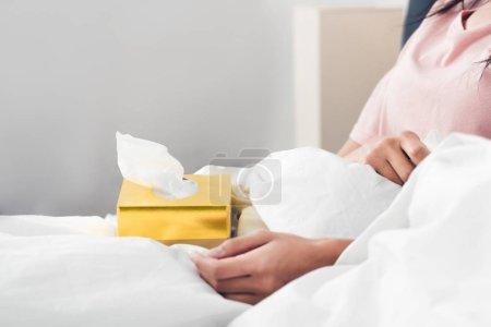 Photo pour Plan recadré de femme malade avec boîte de serviettes en papier assis dans le lit - image libre de droit