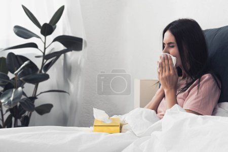 sick young woman with box of paper napkins sitting in bed