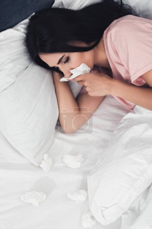 high angle view of sick young woman with runny nose lying in bed with napkins