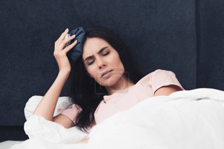 suffering sick young woman holding ice pack on head while lying in bed
