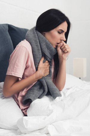 sick young woman sitting in bed and having cough