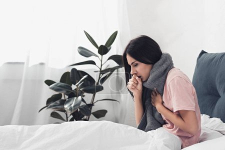 sick young woman sitting in bed and having cough while suffering from sore throat