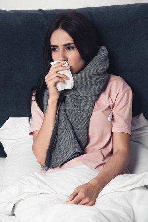 sick young woman covering mouth with napkin during cough in bed