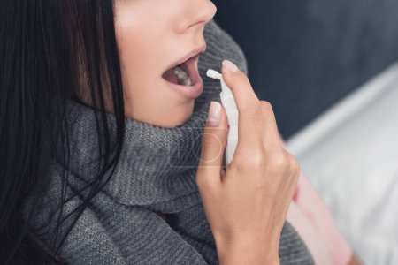 cropped shot of sick young woman in scarf using cough spray
