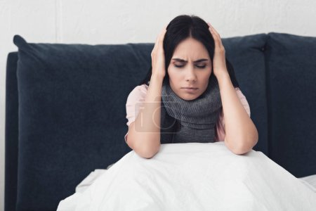 sick young woman sitting in bed and holding head during headache