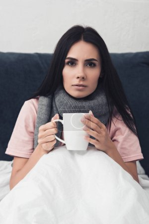 sick young woman in bed holding cup of hot tea while sitting in bed and looking at camera