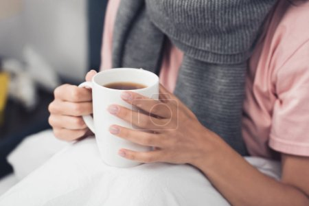 cropped shot of sick woman in bed holding cup of hot tea