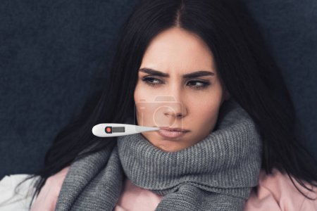 sick young woman measuring temperature with electronic mouth thermometer and looking away
