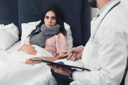 cropped shot of young woman lying in bed while doctor holding clipboard