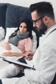 young woman lying in bed while handsome doctor writing in clipboard
