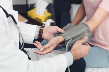 Photo pour Plan recadré du médecin mesurant la pression artérielle du patient - image libre de droit