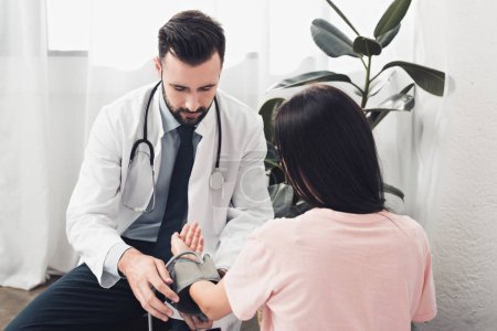 handsome young doctor measuring blood pressure of patient