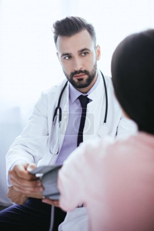 handsome young doctor listening to female patient