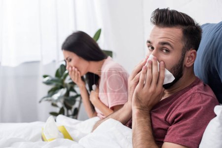 diseased young sick couple sneezing into paper napkins while sitting in bed
