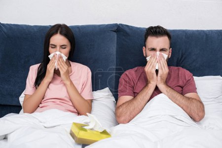 young sick couple sneezing into paper napkins while sitting in bed