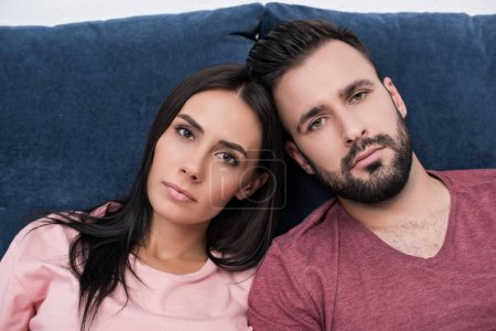 Photo for Unemotional young couple leaning at each other while sitting on couch and looking at camera - Royalty Free Image