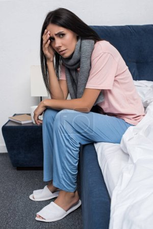sick young woman in scarf suffering from headache while sitting on bed