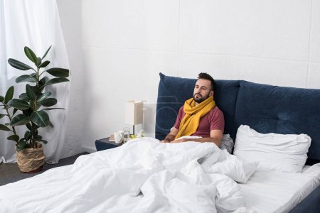 depressed sick young man lying in bed in scarf and looking away