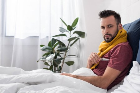 diseased young man measuring temperature with electronic thermometer in bed