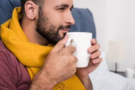close-up portrait of smiling sick young man with scarf holding cup of hot tea in bed