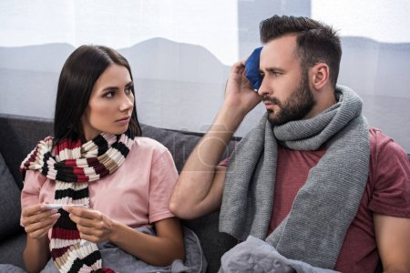 sick young couple with electric thermometer and ice pack sitting together on couch
